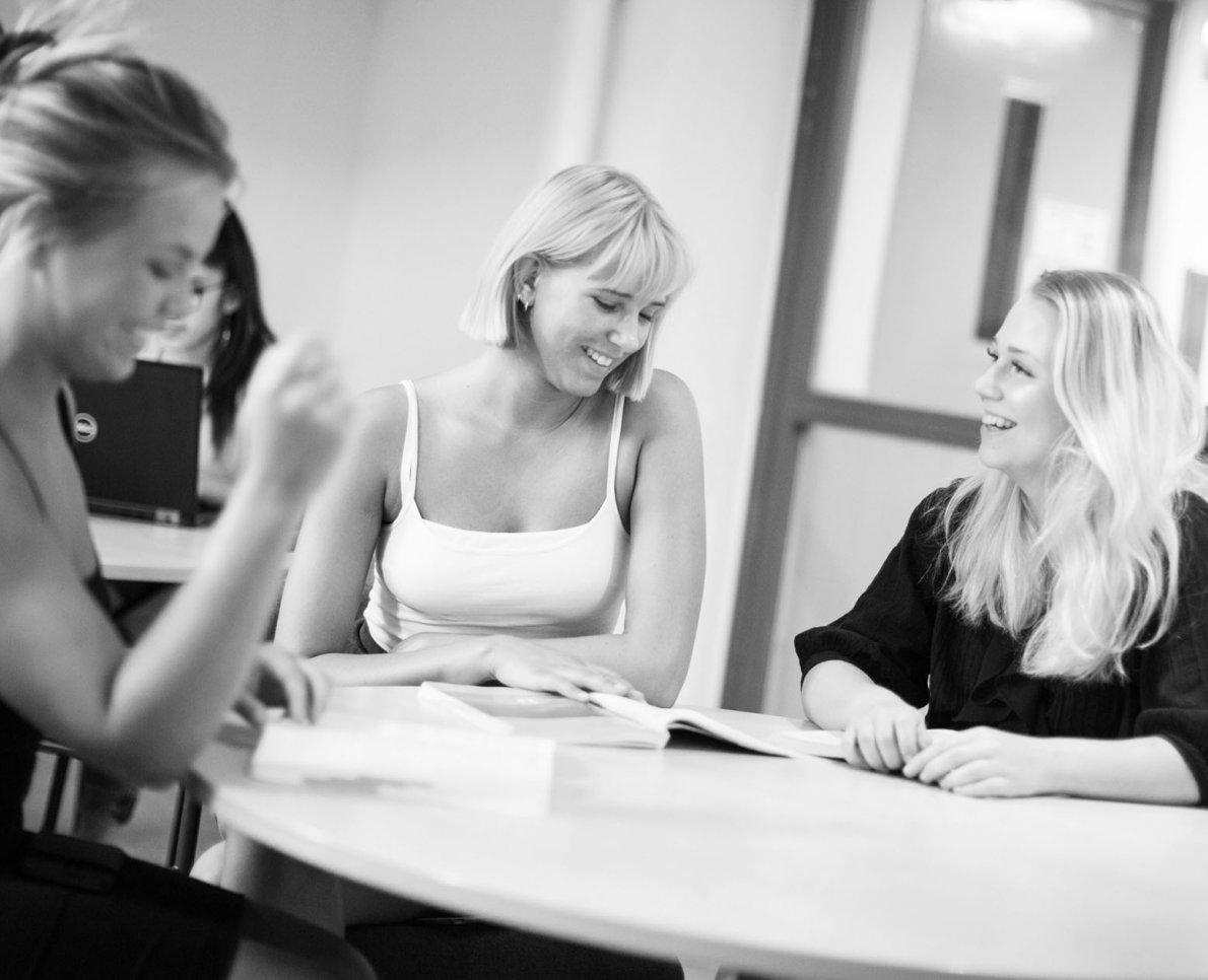 Svartvit bild av tre tjejer som pluggar på Designgymnasiet.