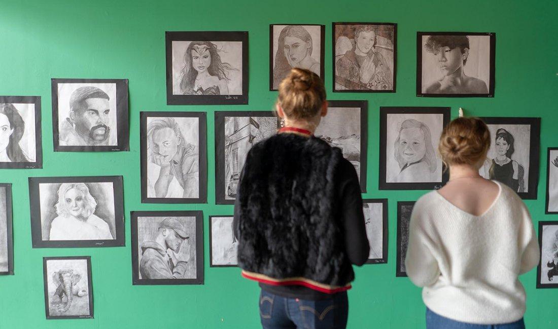 Gymnasieelever kollar på konst som hänger på grön vägg